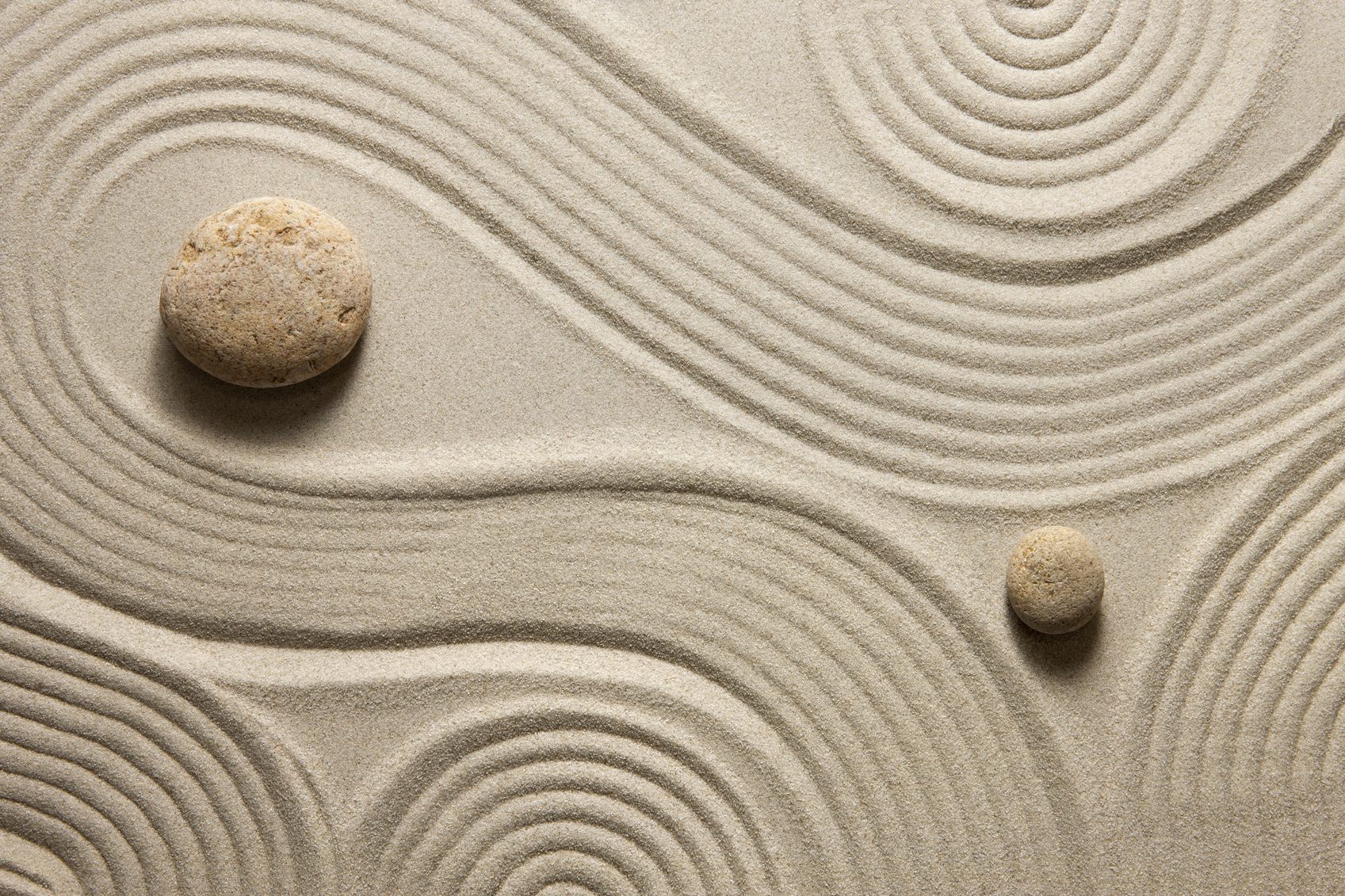 Top view of raked sand with stones